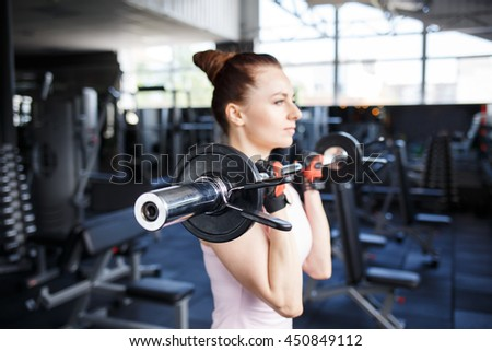 Young beautiful woman doing biceps curl with EZ curl bar in a gym. Athletic girl doing workout in a fitness center - stock photo