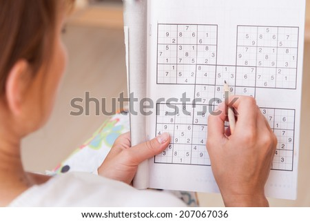 Young  beautiful woman doing crosswords in room - stock photo