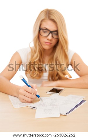 Young beautiful woman doing her accounts, selective focus on the table - stock photo