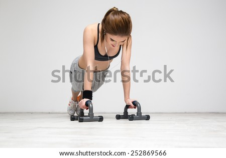 Young beautiful woman doing push ups at gym - stock photo