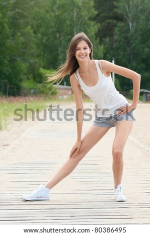 Young beautiful woman doing stretching exercise outdoors - stock photo