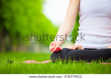 Young beautiful woman doing yoga in the park.