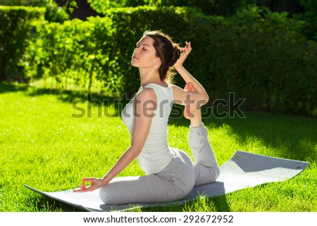Young beautiful woman doing yoga in the park in the morning - stock photo