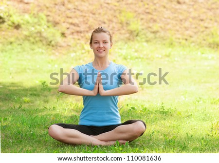 Young beautiful woman doing yoga meditation exercise outdoors