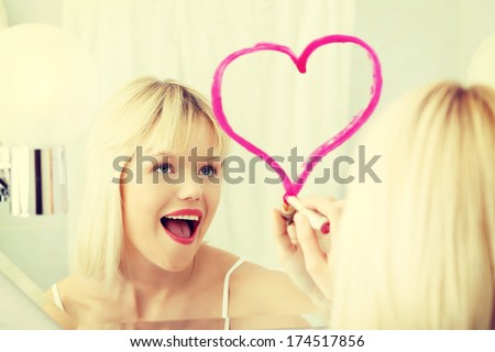 Young beautiful woman drawing big heart on mirror in bathroom. - stock photo