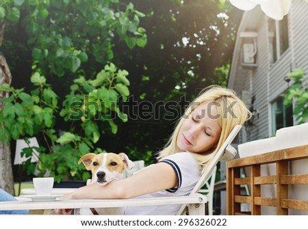 Young beautiful woman drinking a coffee sitting outside in a Rustic Chic cafe with her dog jack russell terrier - stock photo