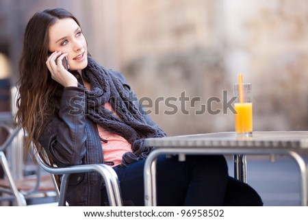 young beautiful woman drinking a orange juice while talking in a bar - stock photo