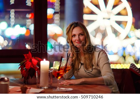 Young beautiful woman drinking champagne cocktail after work in an indoor cafe and restaurant in Paris, France. Christmas market with ferris wheel and lights on background. Happy girl dreaming