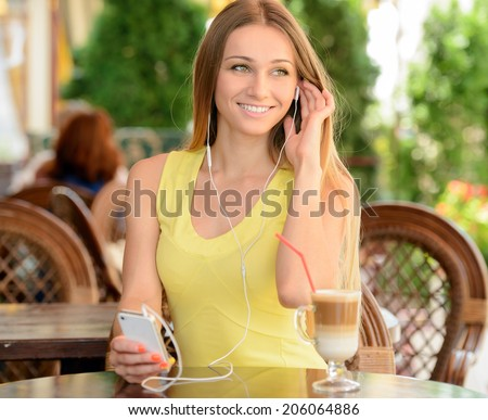 Young beautiful woman drinking coffee and listening to music while sitting in a cafe outdoors - stock photo