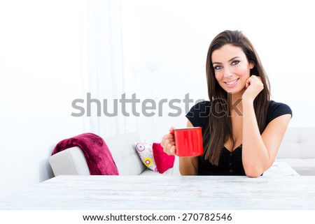Young beautiful woman drinking coffee at home.  - stock photo