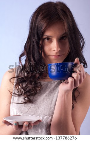 Young beautiful woman drinking from a blue cup - stock photo