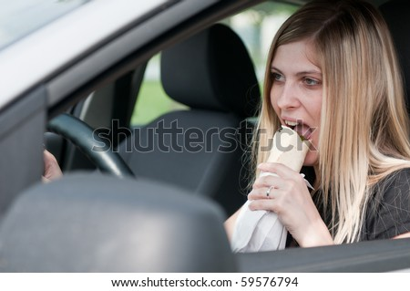 Young beautiful woman driving car and eating fast food with mouth wide open