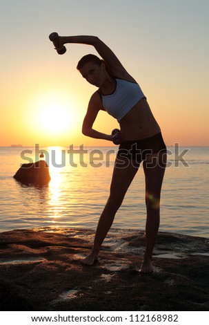 Young beautiful woman during fitness on sea beach - stock photo