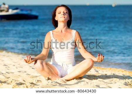 Young beautiful woman during yoga on sea beach - stock photo