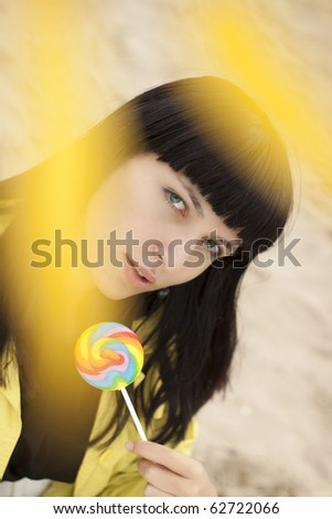Young beautiful woman eating candy. - stock photo
