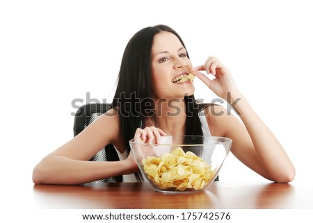 Young beautiful woman eating chips, isolated on white - stock photo