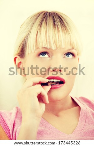 Young beautiful woman eating chocolate.