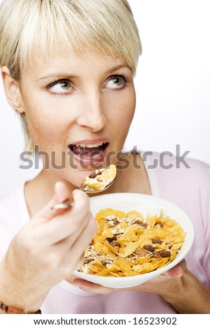 young beautiful woman eating corn flakes close up