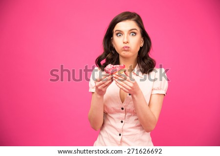 Young beautiful woman eating donut over pink background and looking at camera. Wearing in shirt - stock photo