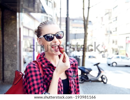 Young beautiful woman eating fresh strawberry. Street photo. Summer time. - stock photo