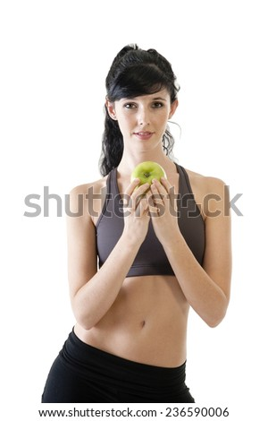 Young beautiful woman eating green apple as part of healthy exercise