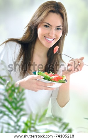 young beautiful woman eating salad - stock photo