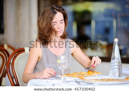 Young beautiful woman eating traditional italian pizza in outdoors restaurant in Venice