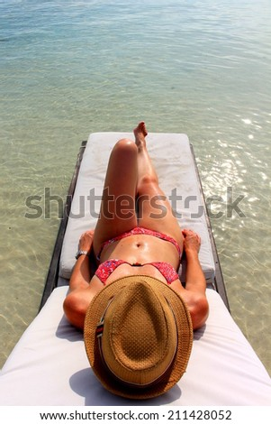 Young beautiful woman enjoying her time and resting close to the sea in Yandup lodge's private beach, Yandup Island, San Blas, Panama - stock photo