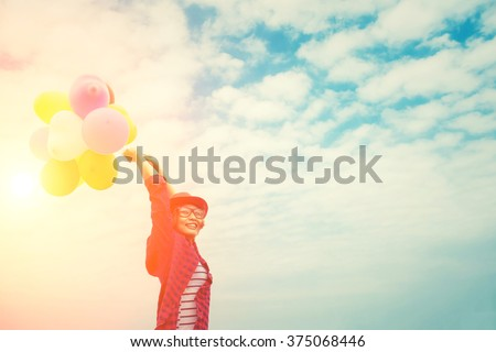 young beautiful woman enjoying Multicolored balloons in the bright sky. - stock photo