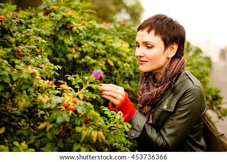 young beautiful woman enjoying the scent of blooming wild rose. The concept of pleasure. - stock photo