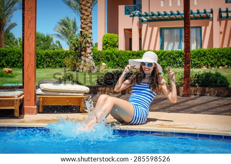 Young beautiful woman enjoying the sun and sitting on edge of the pool. - stock photo