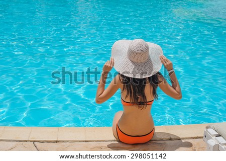 Young beautiful woman enjoying the sun and sitting on edge of the pool - stock photo