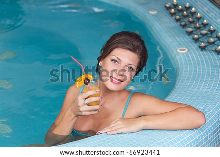 Young beautiful woman enjoying vitamin drinks in jacuzzi - stock photo