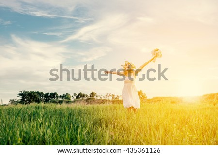 Young beautiful woman enjoying with fresh air at meadows with sunrise