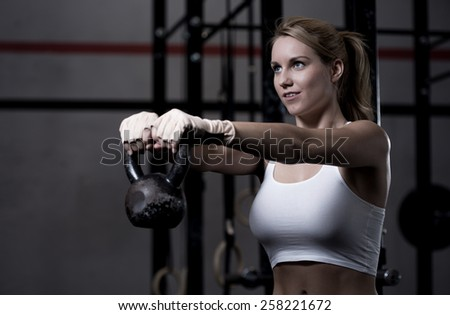 Young beautiful woman exercising with kettlebell - stock photo