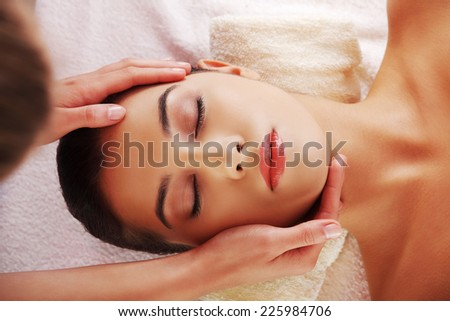 Young beautiful woman face massage in spa