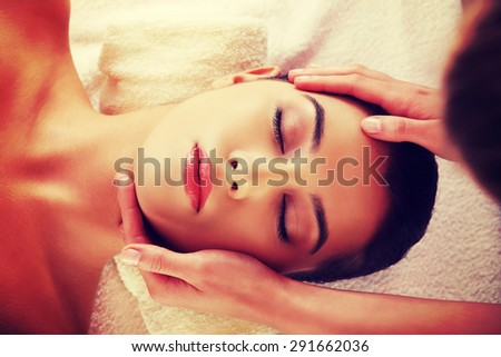 Young beautiful woman face massage in spa - stock photo
