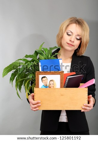 Young beautiful woman fired from her job on grey background