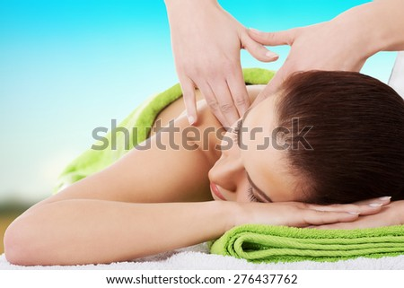 Young beautiful woman getting massage in spa.