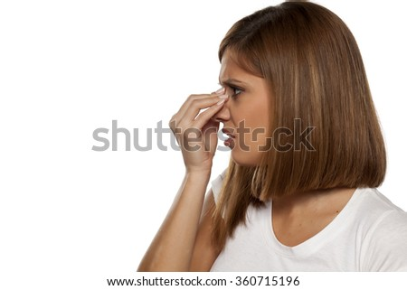 young beautiful woman has pain in the sinuses - stock photo