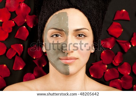 young beautiful woman having a clay mask on half of her face - stock photo