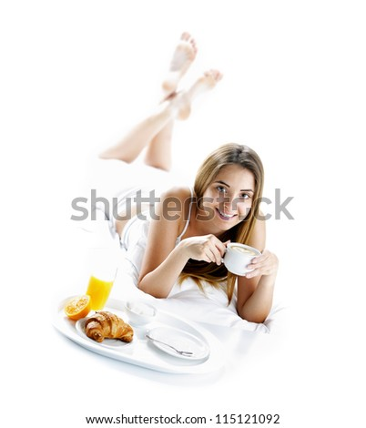 Young beautiful woman having breakfast in bed. - stock photo