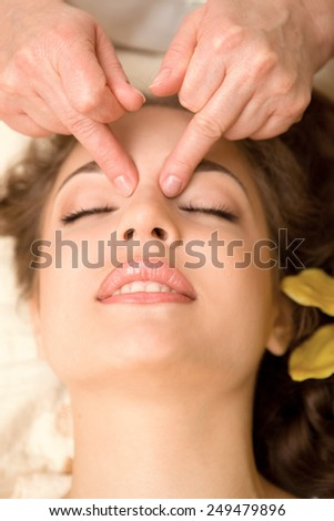Young beautiful woman having facial massage - stock photo