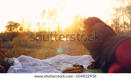 Young beautiful woman having hot tea at sunset relaxing and enjoying nature scene