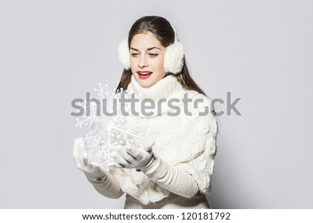young beautiful woman holding a big snowflake, total white look. - stock photo