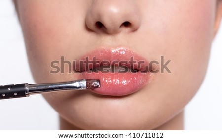 Young beautiful woman holding a brush. Cosmetics. Portrait of a woman on a white background.