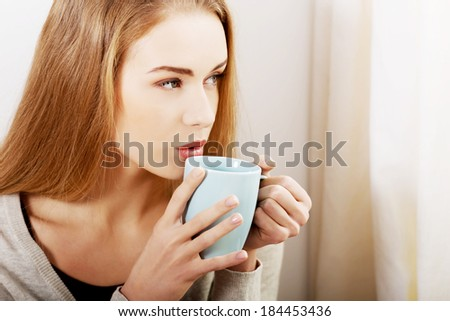Young beautiful woman holding a cup and looking through window. Indoor background. - stock photo