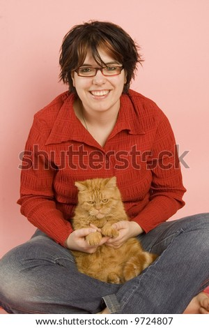 young beautiful woman holding a domestic red cat - stock photo