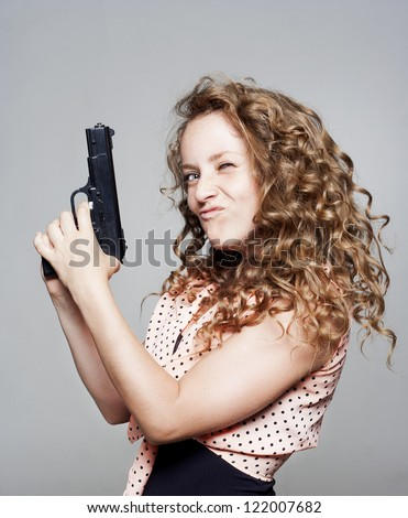 Young beautiful woman holding a gun - stock photo