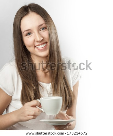 Young beautiful woman holding a mug of coffee - stock photo